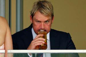 Shane Warne enjoys a drink.